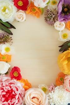 Cornice di fiori freschi colorati su sfondo beige