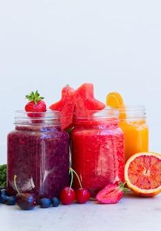 Bevande frullate fresche colorate in barattoli di vetro con ingredienti sul tavolo bianco