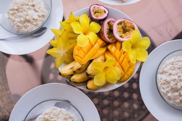 Ciotola di frullato di frutta colorata con frutta fresca cruda e scodelle di fiocchi d'avena
