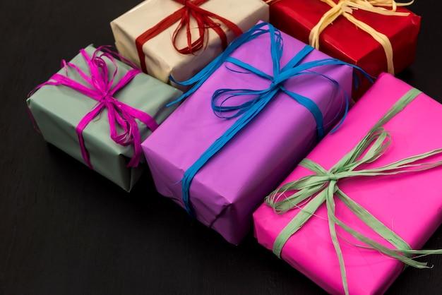 Scatole regalo colorate su sfondo scuro. celebrazione del nuovo anno e del natale