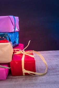 Contenitori di regalo variopinti sulla vista del piano d'appoggio di legno. regali, capodanno e festa di natale