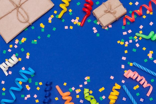 Regali colorati, coriandoli, candele, stelle filanti su sfondo blu. disteso, copia spazio