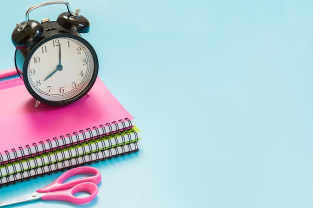 Rifornimenti di scuola, libro e sveglia variopinti di ragazza sull'azzurro incisivo. avvicinamento.
