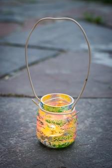 Vaso di vetro colorato con lampada a candela con manico in filo metallico, attività per bambini e concetto di idea artigianale verticale