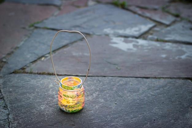 Vaso di vetro colorato con lampada a candela con manico in filo metallico, attività per bambini e concetto di idea fatta a mano