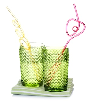 Bicchieri colorati con cannuccia cocktail isolato su superficie bianca