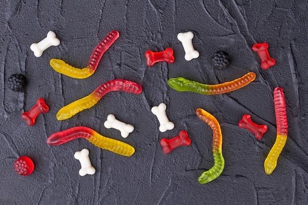 Caramelle gommose colorate su sfondo nero.