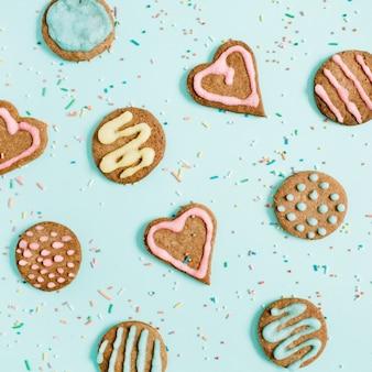 Biscotti e coriandoli fatti a mano variopinti sull'azzurro