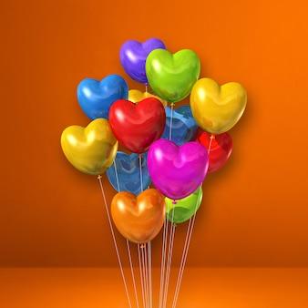 Mazzo di palloncini colorati a forma di cuore sulla parete arancione