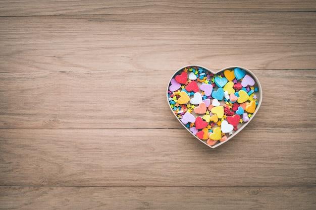 Forma di cuore colorato nella casella sulla tavola di legno