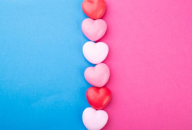 Saponi colorati a forma di cuore su sfondo rosa e blu con spazio di copia.