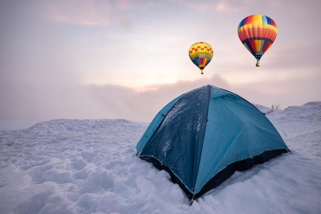 Mongolfiere colorate che volano su una tenda blu in campeggio su una collina innevata