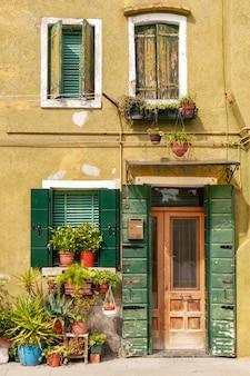 Facciata di casa colorata con persiane in legno su finestre e porte e piante in vaso sul davanzale