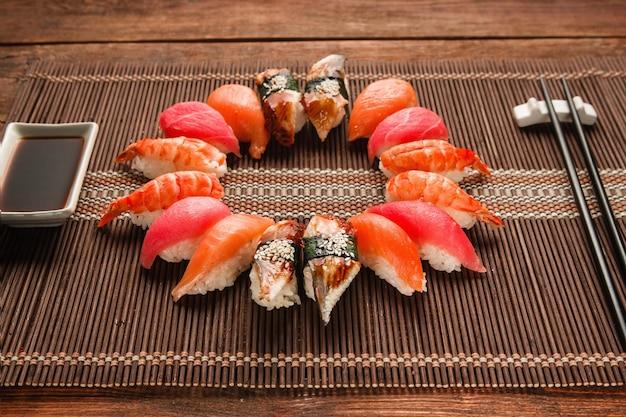 Set di sushi giapponese colorato, frutti di mare. grande assortimento di nigiri nigiri servito come un cerchio su una stuoia di paglia marrone, primo piano. pesce nazionale, foto del menu del ristorante.