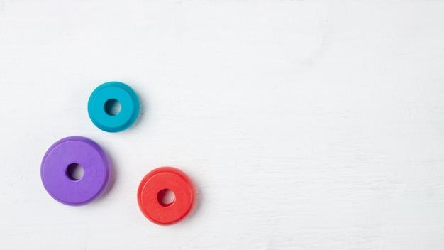 Giocattoli colorati per bambini su bianco in legno. vista dall'alto. disteso. copia spazio per il testo