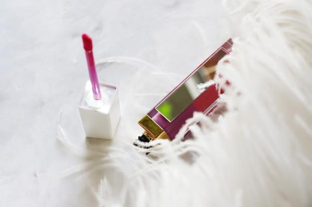 Rossetto colorato con applicatore vicino ad esso. concetto di cosmetici.