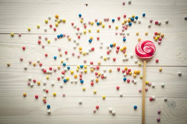 Piccole caramelle colorate e grandi lecca-lecca su fondo di legno bianco