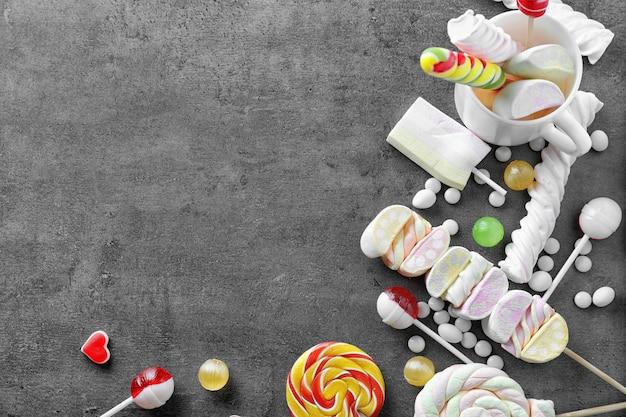 Lecca-lecca colorati con marshmallow su sfondo grigio