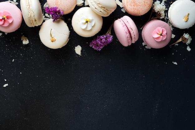 Macarons variopinti su fondo di pietra nero. vista dall'alto con lo spazio della copia.