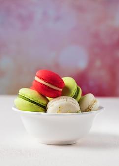 Biscotti variopinti dei macarons in ciotola bianca su fondo pastello, spazio della copia.