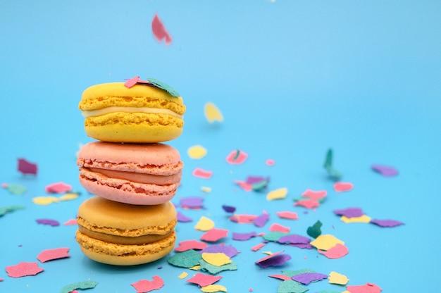 Macarons colorati su carta blu pastello alla moda con coriandoli. gustosi amaretti rosa, gialli e marroni.