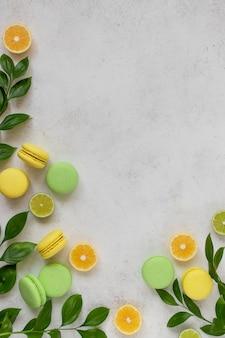 Macarons colorati con rami verdi, fette di limone, superficie bianca lime