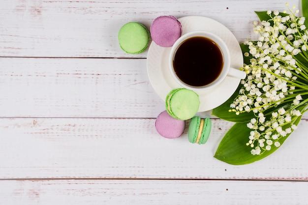 Amaretti colorati una tazza di caffè e mughetti su fondo di legno piatto piano primo piano