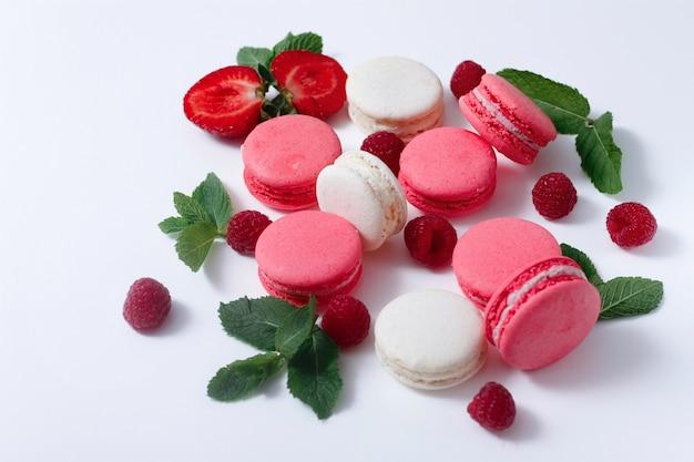 Amaretti colorati sul piatto bianco, rosa, con frutti di bosco, menta
