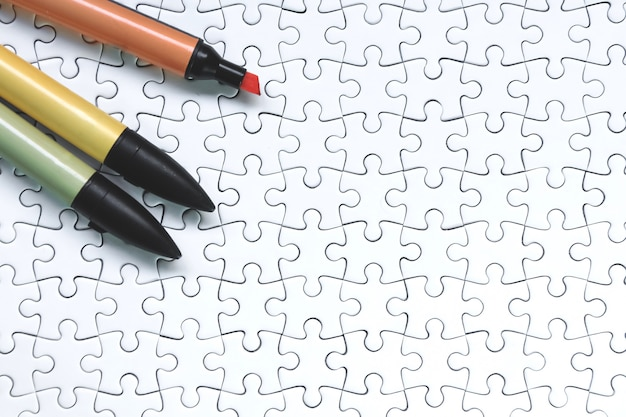 Pennarelli colorati su puzzle bianco