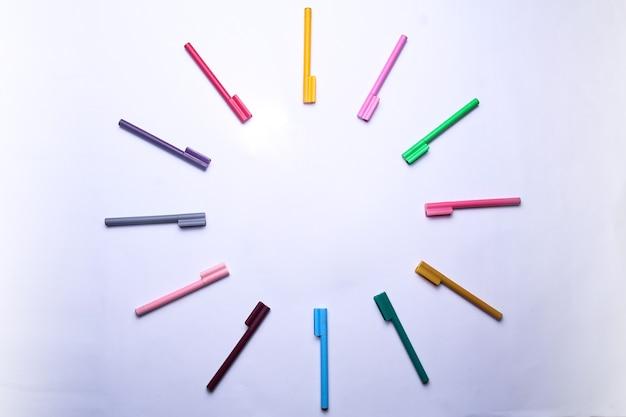 I pennarelli colorati formano un cerchio in uno sfondo bianco isolato vista dall'alto