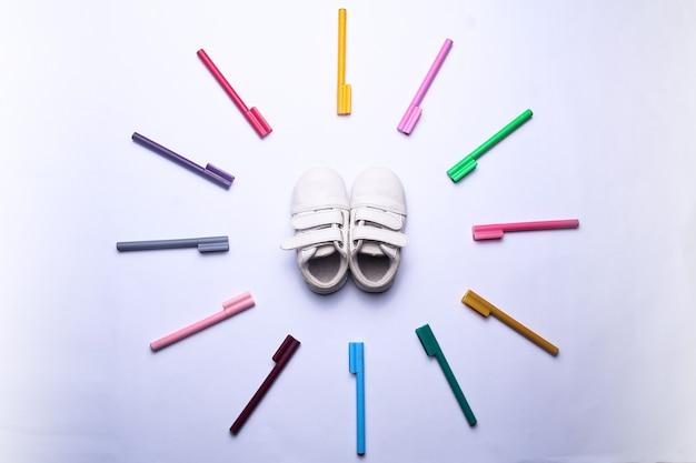 I pennarelli colorati formano un cerchio che circonda le scarpe per bambini in uno sfondo bianco isolato vista dall'alto