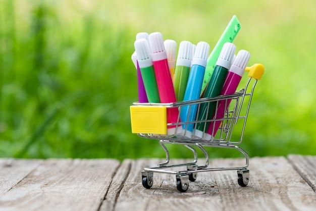 Pennarelli colorati e un righello in un piccolo carrello della spesa