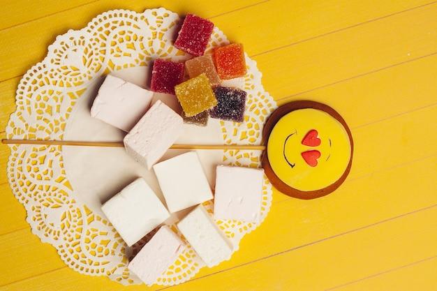 Colorata marmellata di arance caramelle dolci dessert godimento sfondo giallo. foto di alta qualità