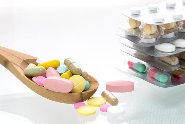 Pillole colorate delle medicine sul cucchiaio e sulla compressa della medicina su fondo bianco