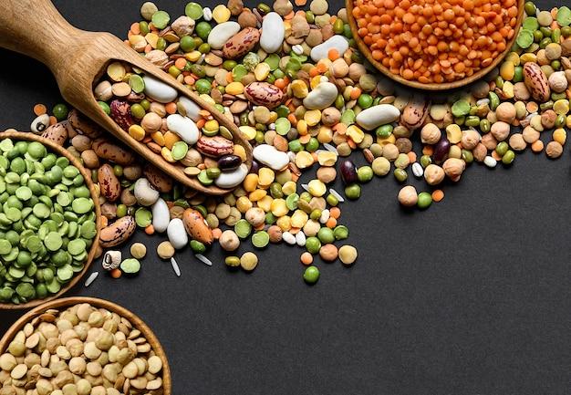 Colorati legumi misti e cereali mucchio con ciotole di legno e paletta su sfondo nero. vista dall'alto. copia spazio