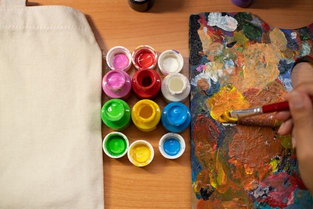 Barattoli di vernice colorati per l'artigianato accanto alla tavolozza del pittore