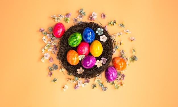 Nido dell'uovo di pasqua dipinto colorato con vista dall'alto di sfondo colorato pastello arancione