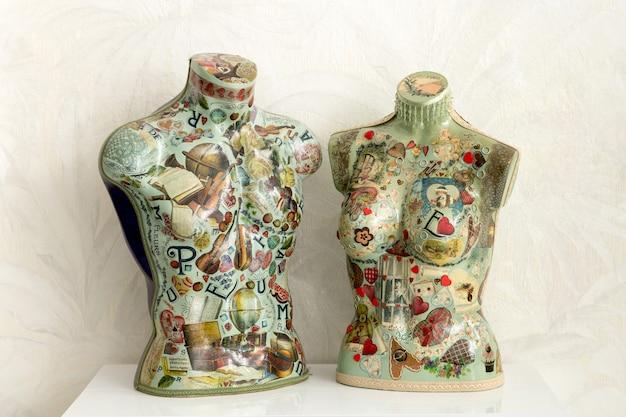 Coloratissima coppia di busti di manichino vintage su un tavolo con decoro in decoupage in forma maschile e femminile
