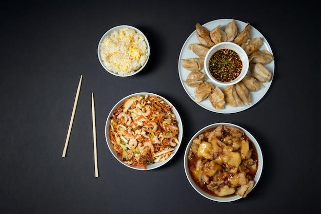 Tavolozza colorata di cibo asiatico da asporto - insalata di gamberi, pollo croccante dolce, riso e gnocchi fritti su sfondo nero