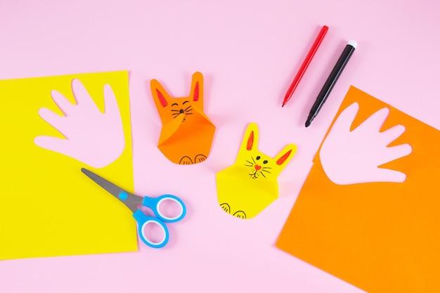 Coniglietti di carta colorati dai palmi delle mani dei bambini su sfondo colorato