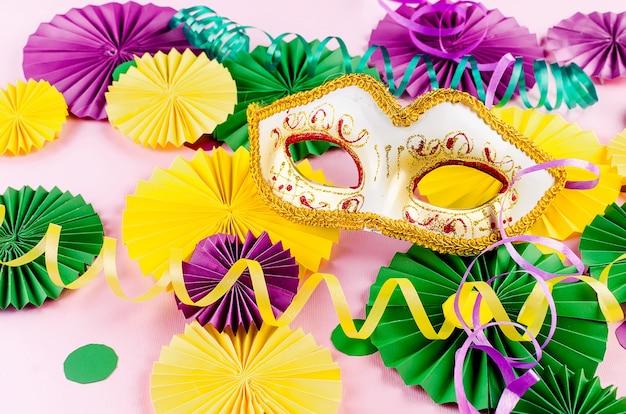 Coriandoli di carta colorati, maschera carnivale e serpentina colorata su sfondo giallo