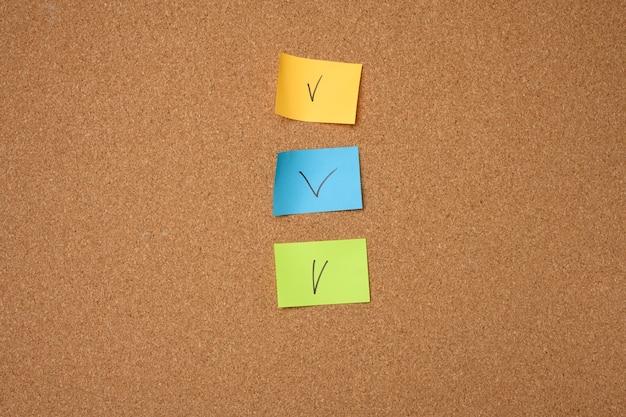 Adesivi di carta colorati incollati alla bacheca di sughero marrone, da vicino