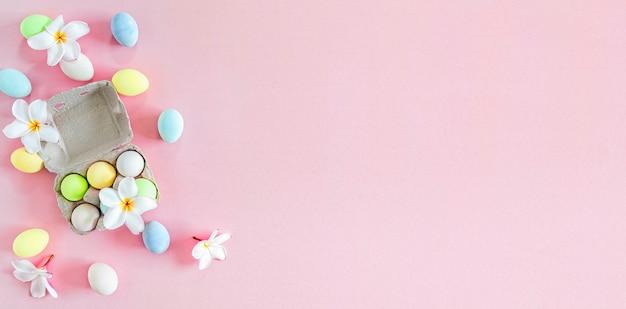 Colorate uova di pasqua pastello con fiori di frangipane bianco su sfondo rosa, vista dall'alto con luce naturale. stile piatto.