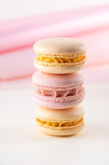 Macarons o macarons francesi pastelli variopinti su fondo bianco e rosa