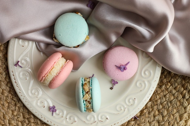 Amaretti francesi pastelli colorati su un piatto bianco con tessuto di lavanda su di una superficie di paglia