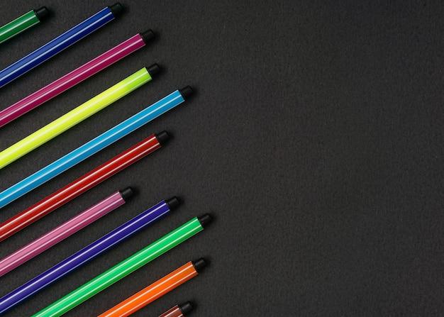 Penna colorata su sfondo nero. disposizione piatta. copia spazio.