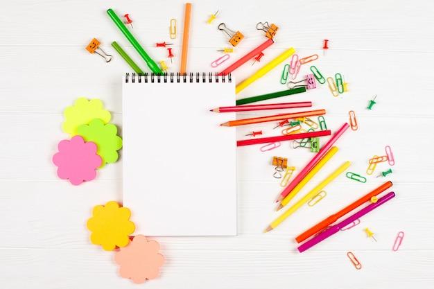 Matite colorate e pennarelli, carta da lettere e cancelleria su fondo di legno bianco.