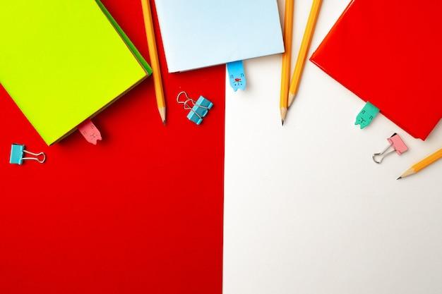 Matite colorate e taccuini su sfondo di carta vista dall'alto, copia dello spazio