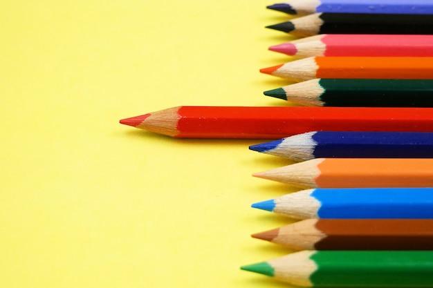 Matite colorate crude con una matita rossa in piedi fuori dalla folla su sfondo giallo