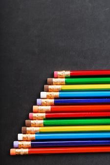 Matite colorate con gomme in fila su sfondo nero